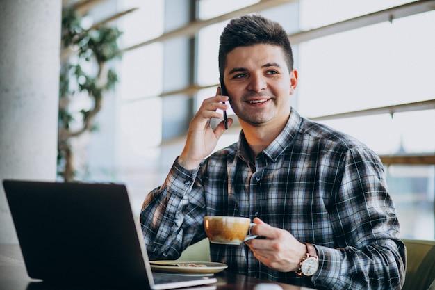 Junger hübscher geschäftsmann, der laptop in einem café verwendet Kostenlose Fotos