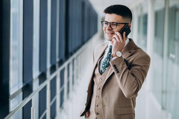 Junger hübscher geschäftsmann, der mit telefon im büro steht Kostenlose Fotos