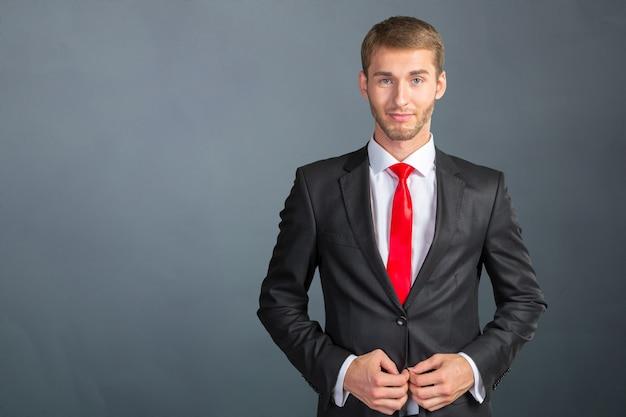 Junger hübscher geschäftsmann, der seine bindung justiert Premium Fotos