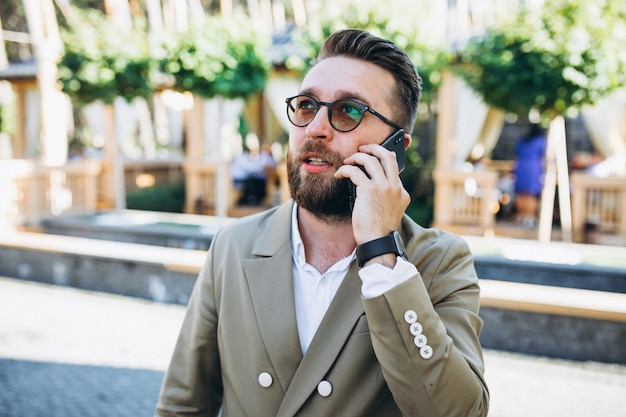 Junger hübscher geschäftsmann, der telefon verwendet Kostenlose Fotos