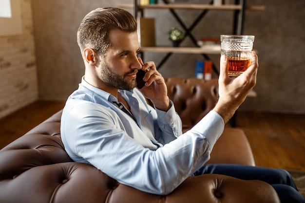 Junger hübscher geschäftsmann sitzt auf sofa und betrachtet glas des whiskys in der hand in seinem eigenen büro. guy telefoniert. ernst und konzentriert. sexy junger mann. Premium Fotos