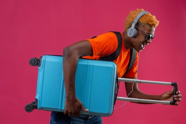 Junger hübscher junge, der orange t-shirt mit kopfhörern auf kopf hält, der reisekoffer hält Kostenlose Fotos
