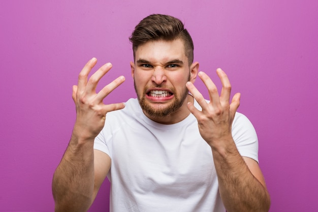Junger hübscher kaukasischer mann störte das schreien mit den angespannten händen. Premium Fotos