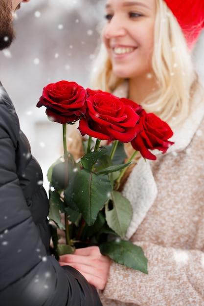 Junger hübscher kerl, der einem mädchen einen strauß rosen am valentinstag gibt Premium Fotos