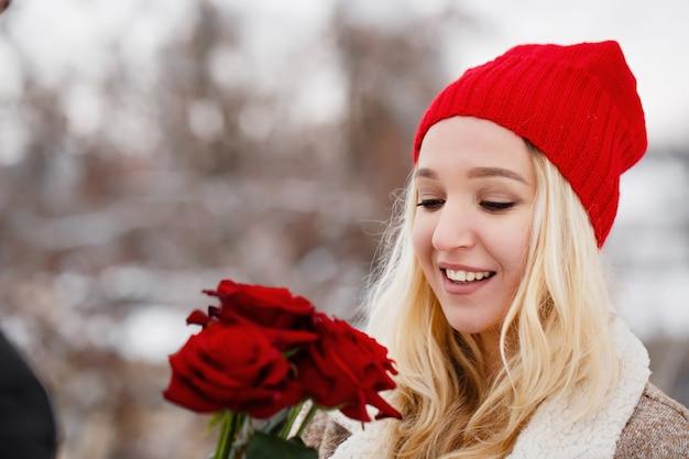 Junger hübscher kerl, der einer frau einen strauß rosen am valentinstag gibt Premium Fotos