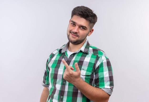 Junger hübscher kerl, der kariertes hemd trägt, das fickzeichen mit mittelfinger über weißer wand zeigt Kostenlose Fotos