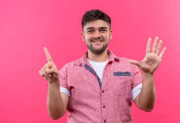 Junger hübscher kerl, der rosa poloshirt trägt, zeigt glücklich sechs mit den fingern, die über rosa wand stehen Kostenlose Fotos
