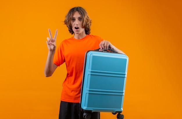 Junger hübscher kerl im orangefarbenen t-shirt, der reisekoffer hält, der nummer zwei oder siegeszeichen zeigt, das überrascht steht Kostenlose Fotos