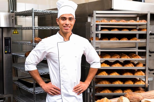 Junger hübscher männlicher bäcker in der weißen uniform, die gegen backregal steht Kostenlose Fotos