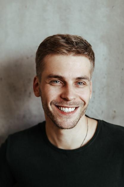 Junger hübscher mann, der aufwirft   Kostenlose Foto