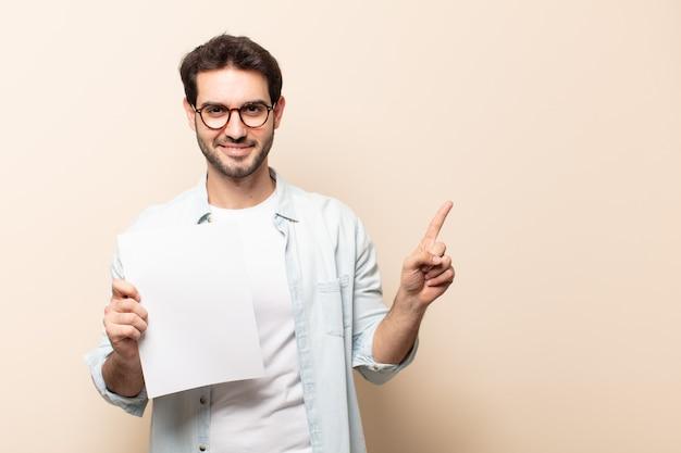 Junger hübscher mann, der fröhlich lächelt, sich glücklich fühlt und zur seite und nach oben zeigt, objekt im kopienraum zeigt Premium Fotos