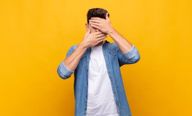 Junger hübscher mann, der gesicht mit beiden händen bedeckt, sagt nein zur kamera! Premium Fotos