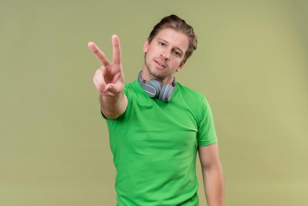 Junger hübscher mann, der grünes t-shirt mit lächelnden kopfhörern trägt und mit den fingern nummer zwei oder siegeszeichen über grüner wand zeigend zeigt Kostenlose Fotos