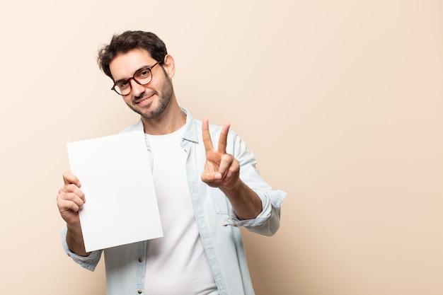 Junger hübscher mann, der lächelt und glücklich, sorglos und positiv schaut, sieg oder frieden mit einer hand gestikulierend Premium Fotos