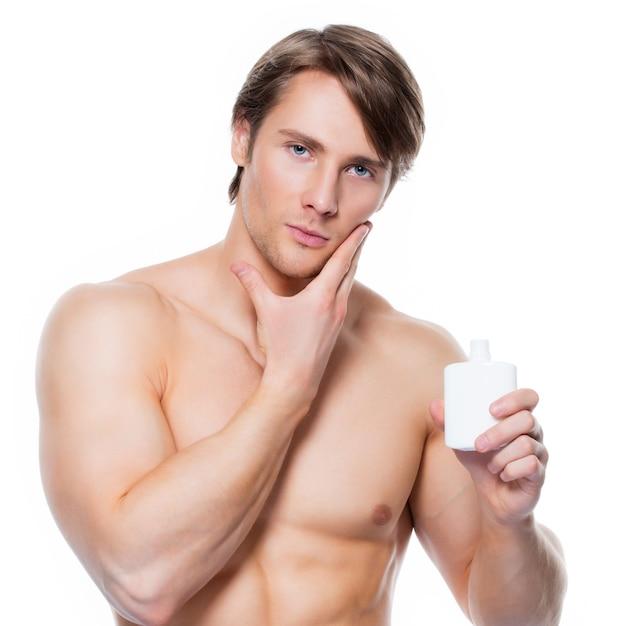 Junger hübscher mann, der lotion auf gesicht aufträgt - lokalisiert auf weiß. Kostenlose Fotos
