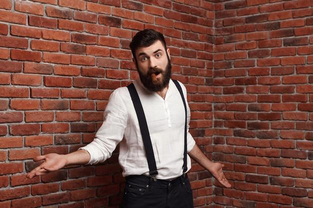 Junger hübscher mann, der rauchende zigarre auf ziegelmauer gestikuliert. Kostenlose Fotos