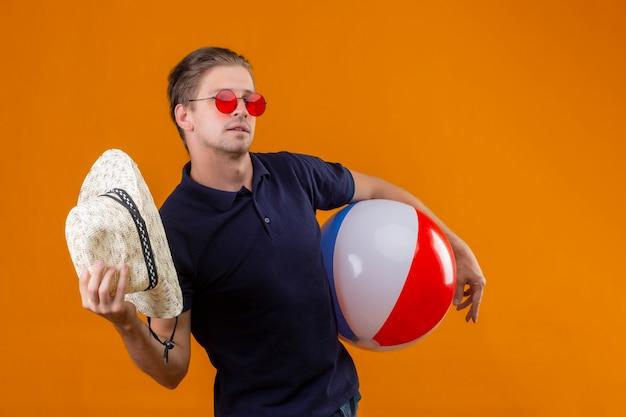 Junger hübscher mann, der rote sonnenbrille trägt, die mit aufblasbarem ball steht, der mit strohhut winkt, der über orange hintergrund zuversichtlich schaut Kostenlose Fotos