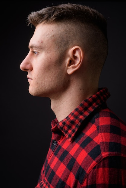 Junger hübscher mann, der rotes kariertes hemd auf grau