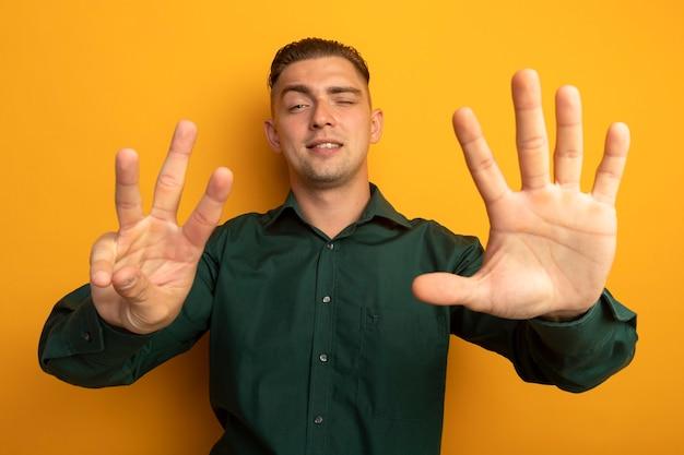 Junger hübscher mann im grünen hemd, das mit dem finger nummer acht zeigt und oben zeigt, der zuversichtlich lächelt Kostenlose Fotos