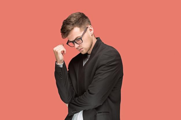 Junger hübscher mann im schwarzen anzug und in den gläsern lokalisiert auf roter wand Kostenlose Fotos