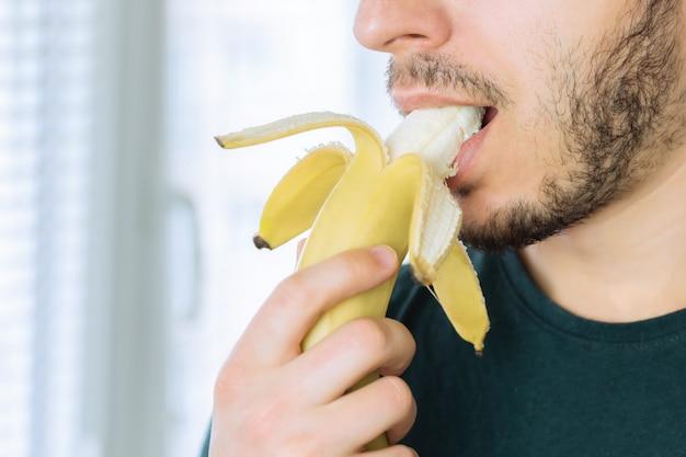 Junger hübscher mann mit einem bart, der eine banane abbeißt, die in der küche steht. Premium Fotos