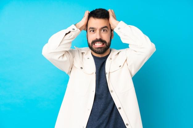 Junger hübscher mann mit weißer cordjacke über blau frustriert und nimmt hände auf kopf Premium Fotos