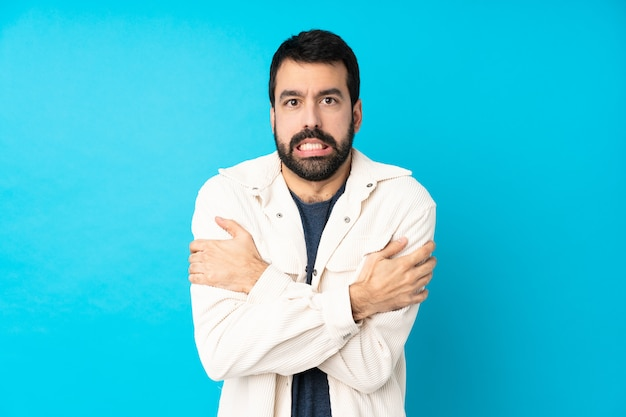 Junger hübscher mann mit weißer cordjacke über blauem gefrieren Premium Fotos