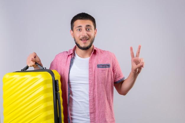 Junger hübscher reisender kerl, der koffer hält, der kamera betrachtet, die glücklich und positiv lächelt und nummer zwei oder siegeszeichen zeigt, das über weißem hintergrund steht Kostenlose Fotos