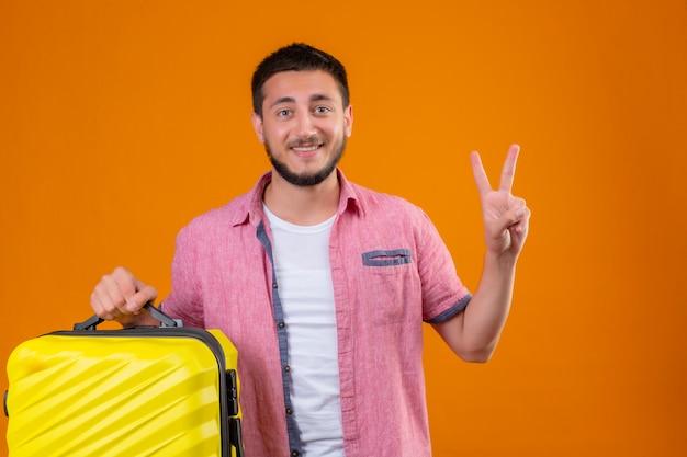 Junger hübscher reisender kerl, der koffer hält kamera mit glücklichem gesicht lächelnd zeigt nummer zwei oder siegeszeichen steht über orange hintergrund Kostenlose Fotos