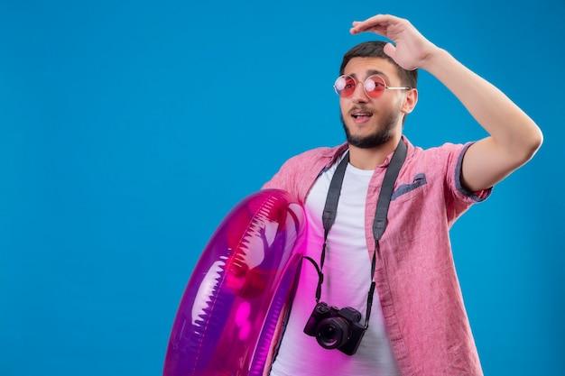 Junger hübscher reisender kerl, der sonnenbrillen steht, die mit aufblasbarem ring stehen und beiseite winken mit hand glücklich und positiv über blauem hintergrund winken Kostenlose Fotos
