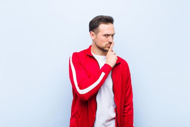 Junger hübscher sportmann oder -monitor, die um ruhe und ruhe bitten, mit dem finger vor mund gestikulieren, shh sagen oder ein geheimnis gegen grüne wand halten Premium Fotos