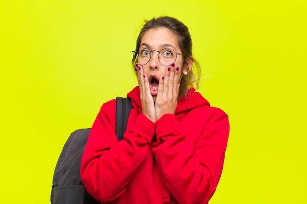 Junger hübscher student, der entsetzt und erschrocken sich fühlt und mit offenem mund und den händen auf backen erschrocken schaut Premium Fotos