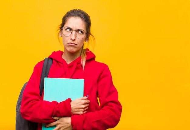 Junger hübscher student, der traurig, verärgert oder verärgert sich fühlt und zur seite mit einer negativen haltung schaut und in der uneinigkeit die stirn runzelt Premium Fotos