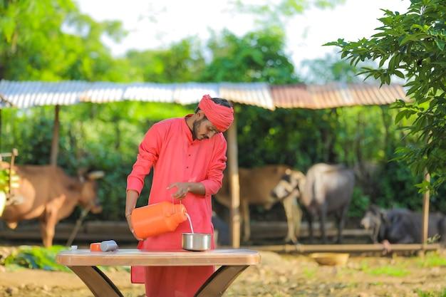 Junger indischer bauer am milchviehbetrieb Premium Fotos