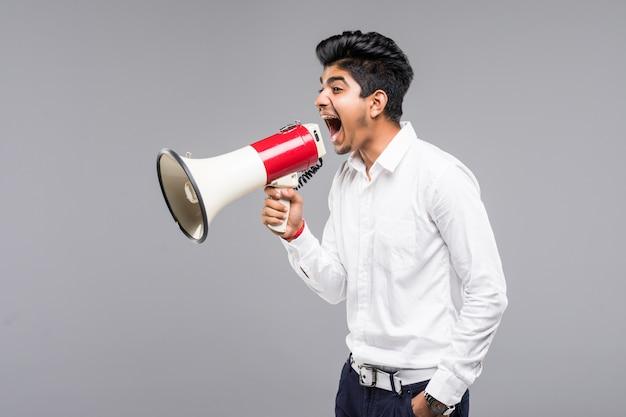 Junger indischer geschäftsmann, der in ein megaphon auf grauer wand ankündigt Kostenlose Fotos
