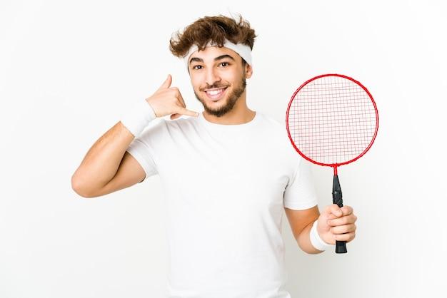 Junger indischer mann, der badminton spielt, zeigt eine handy-anrufgeste mit den fingern. Premium Fotos
