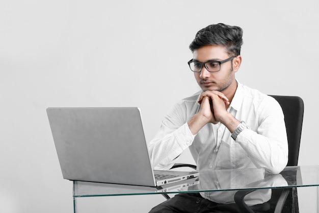 Junger indischer mann, der im büro arbeitet Premium Fotos