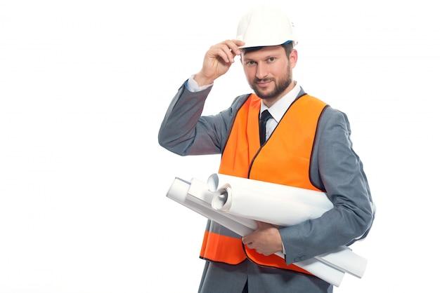 Junger ingenieur lächelnd, weißen sicherheitshut durch hand haltend. Kostenlose Fotos