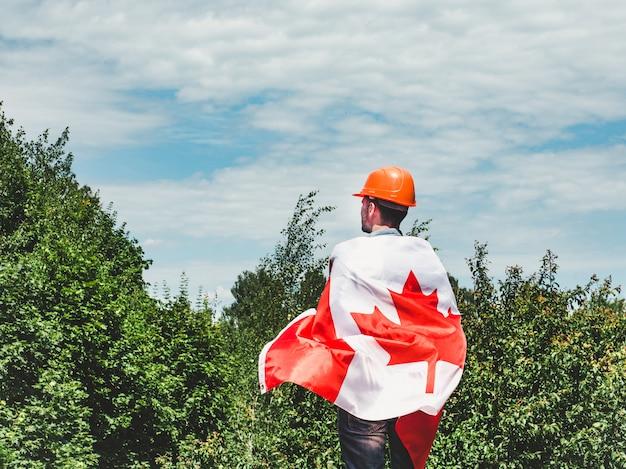 Junger ingenieur, orange hardhat und kanadische flagge Premium Fotos