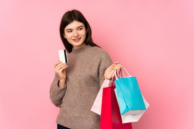 Junger jugendlicher, der einkaufstaschen und eine kreditkarte hält Premium Fotos