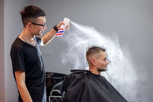Junger kasachischer friseur arbeitet in einem friseursalon, ein junger mann macht einen kurzen haarschnitt bei einem friseur, macht sich nass, wasser spritzt auf einem grauen wandhintergrund Premium Fotos
