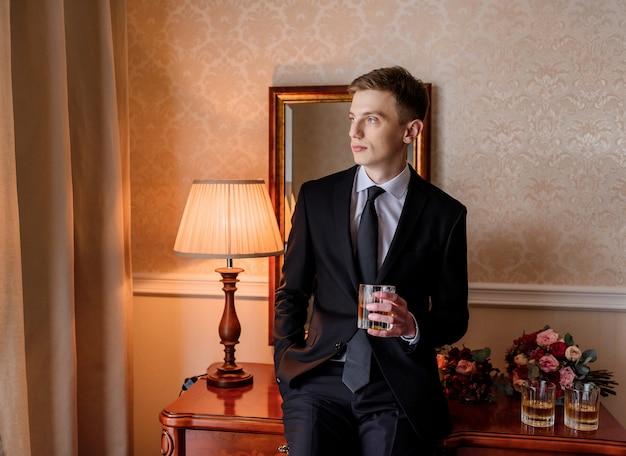 Junger kaukasischer bräutigam gekleidet im stilvollen smoking, der alkohol im zimmer trinkt und auf dem tisch neben brautsträußen sitzt Kostenlose Fotos