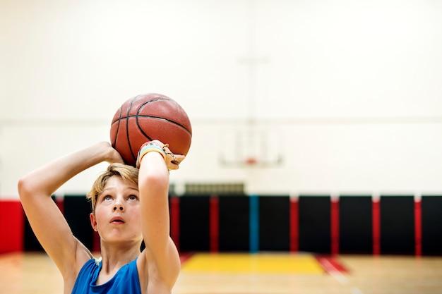 Junger kaukasischer junge, der schießenbasketball im stadion spielt Kostenlose Fotos