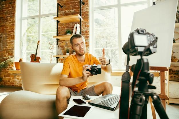 Junger kaukasischer männlicher blogger mit professioneller ausrüstung, die videoüberprüfung der kamera zu hause aufzeichnet. bloggen, videoblog, vloggen. mann, der vlog oder live-stream über foto oder technische neuheit macht. Kostenlose Fotos