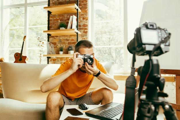 Junger kaukasischer männlicher blogger mit professioneller ausrüstung, die videoüberprüfung der kamera zu hause aufzeichnet Kostenlose Fotos