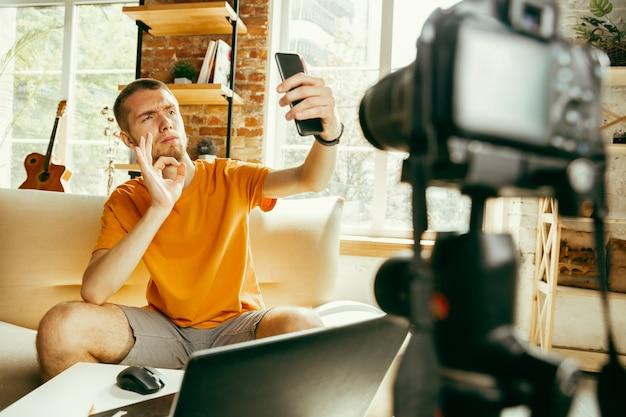 Junger kaukasischer männlicher blogger mit professioneller kameraaufzeichnung videoüberprüfung des smartphones zu hause Kostenlose Fotos