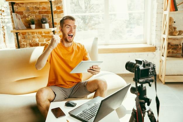 Junger kaukasischer männlicher blogger mit professioneller kameraaufzeichnung videoüberprüfung des tablets zu hause Kostenlose Fotos