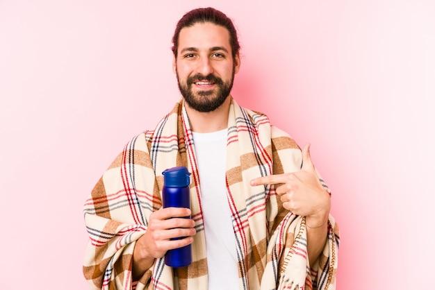 Junger kaukasischer mann an einem kampierenden tag eine thermosflasche halten, die eigenhändig auf einen hemdkopienraum, stolz und überzeugt zeigt Premium Fotos