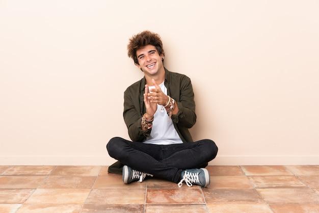 Junger kaukasischer mann, der auf dem boden applaudiert nach darstellung in einer konferenz sitzt Premium Fotos