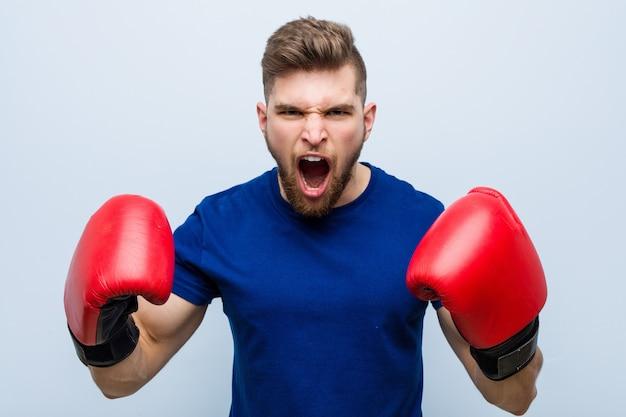 Junger kaukasischer mann, der boxhandschuhe trägt Premium Fotos